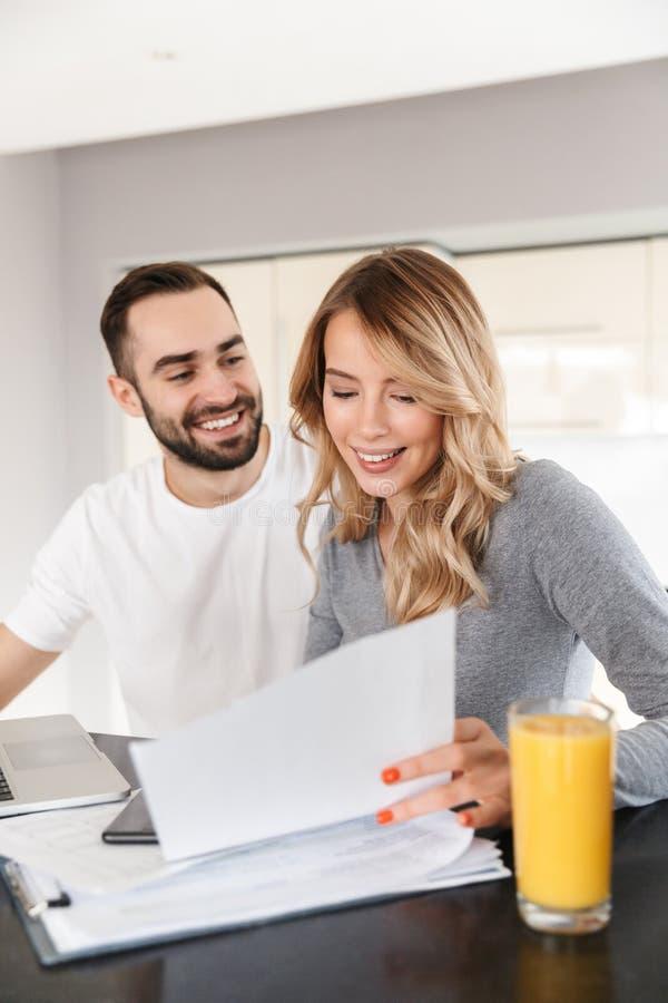 Pares de amor que sentam-se na cozinha usando o laptop e no trabalho com documentos foto de stock royalty free