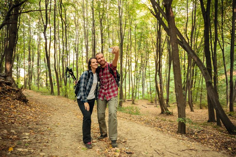 Pares de amor que tomam um selfie ao caminhar através da floresta em um dia bonito do outono Saudável e ativo imagens de stock royalty free