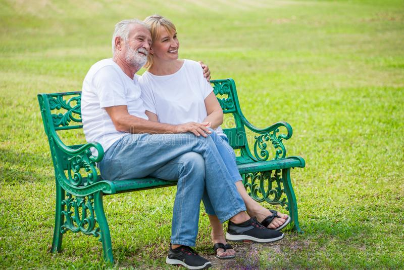 Pares de amor superiores felizes que relaxam no parque que abraça junto no tempo de manhã pessoas adultas que sentam-se em um ban fotografia de stock royalty free