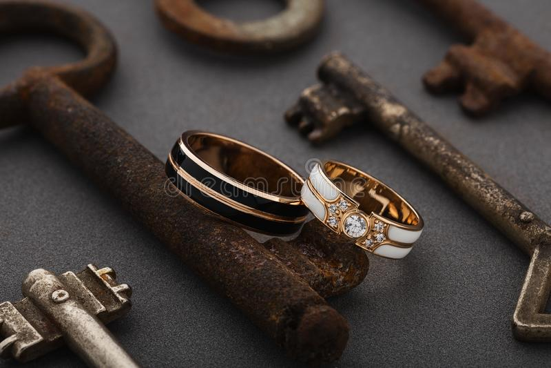 Pares de anéis do esmalte do casamento no fundo cinzento com chaves oxidadas do vintage fotografia de stock