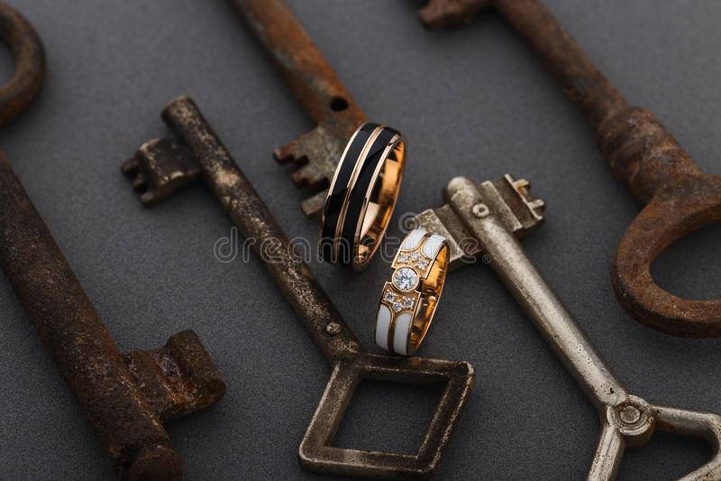 Pares de anéis do esmalte do casamento no fundo cinzento com chaves oxidadas do vintage imagem de stock royalty free