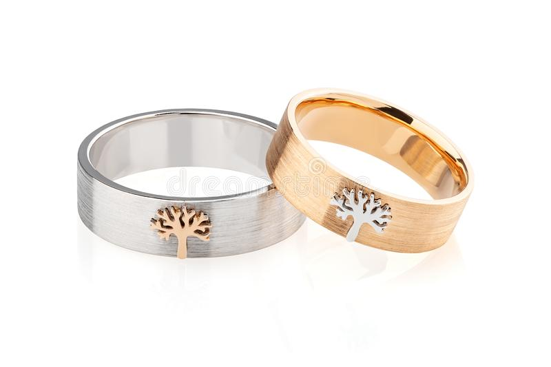 Pares de anillo para hombre de plata y de anillo para mujer del oro del rosa con el árbol en el fondo blanco imagen de archivo libre de regalías