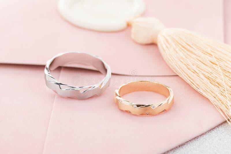 Pares de anillo para hombre de plata y de anillo para mujer del oro del rosa con los diamantes en sobre rosado de la invitación fotografía de archivo
