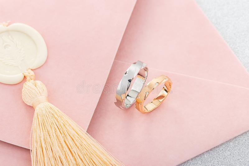Pares de anillo para hombre de plata y de anillo para mujer del oro del rosa con los diamantes en sobre rosado de la invitaci?n foto de archivo libre de regalías