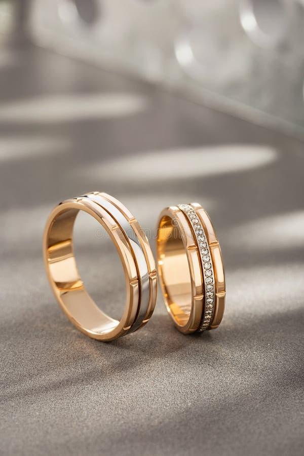 Pares de anillos de bodas del oro con los diamantes en fondo gris con las sombras fotografía de archivo libre de regalías