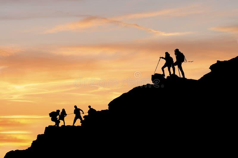 Pares de Asia que caminan ayuda silueta en montañas con luz del sol pares que caminan ayuda silueta en montañas imagen de archivo
