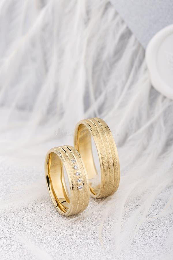 Pares de bandas superficiales texturizadas del anillo de bodas del oro en el fondo blanco foto de archivo