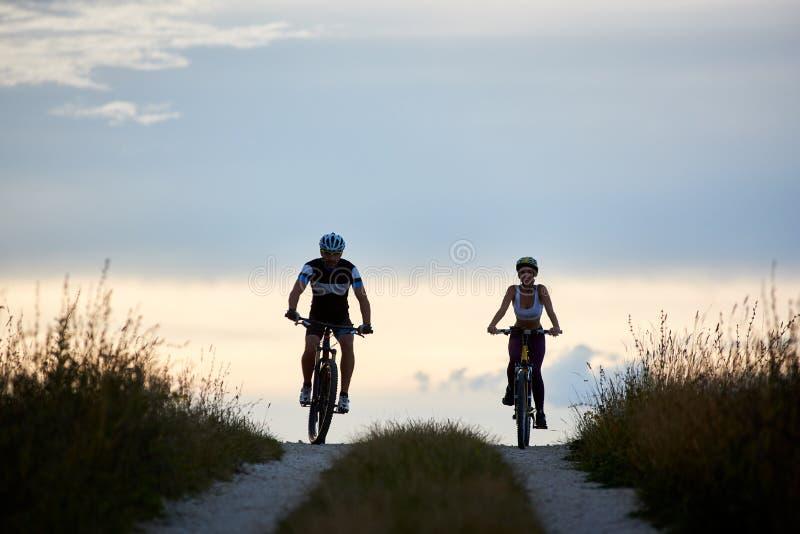 Pares de bicicletas da equitação do ciclista na estrada secundária Jovens aptos no sportswear que dá um ciclo para baixo imagem de stock