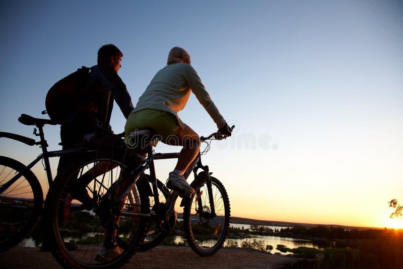 Pares de bicicletas en puesta del sol imágenes de archivo libres de regalías
