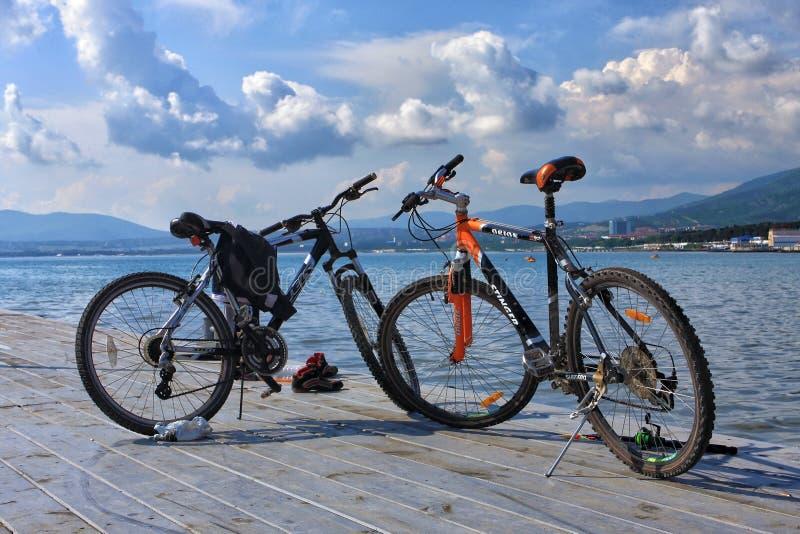 Pares de bicis de montaña que se colocan en el embarcadero del Mar Negro en fondo escénico de la playa imagen de archivo