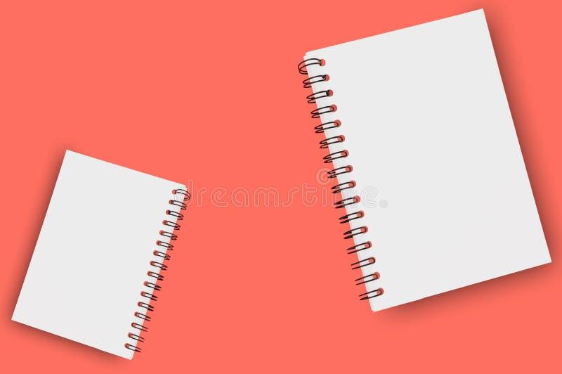 Pares de blocos de notas de papel vazios com fio espiral para a nota ou desenho no fundo da cor coral de vida Copie o espaço para foto de stock