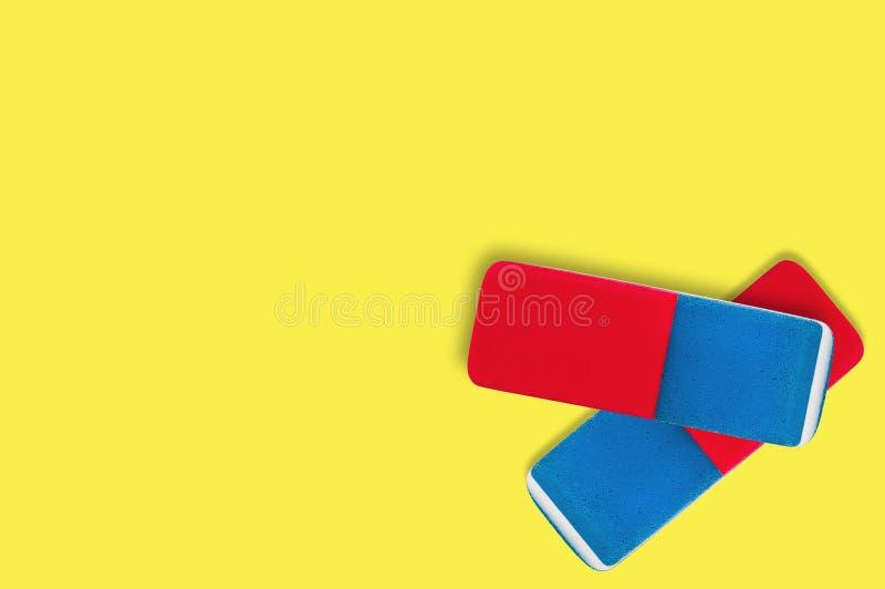 Pares de borradores de goma rectangulares para el lápiz y la tinta de la pluma en fondo amarillo fotos de archivo libres de regalías