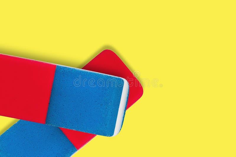 Pares de borradores de goma rectangulares para el lápiz y la tinta de la pluma en fondo amarillo fotografía de archivo libre de regalías