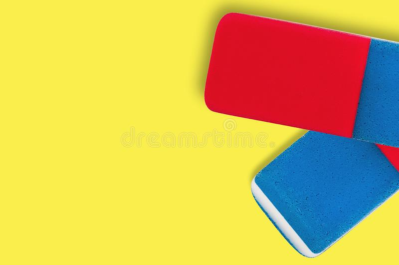 Pares de borradores de goma rectangulares para el lápiz y la tinta de la pluma en fondo amarillo fotos de archivo