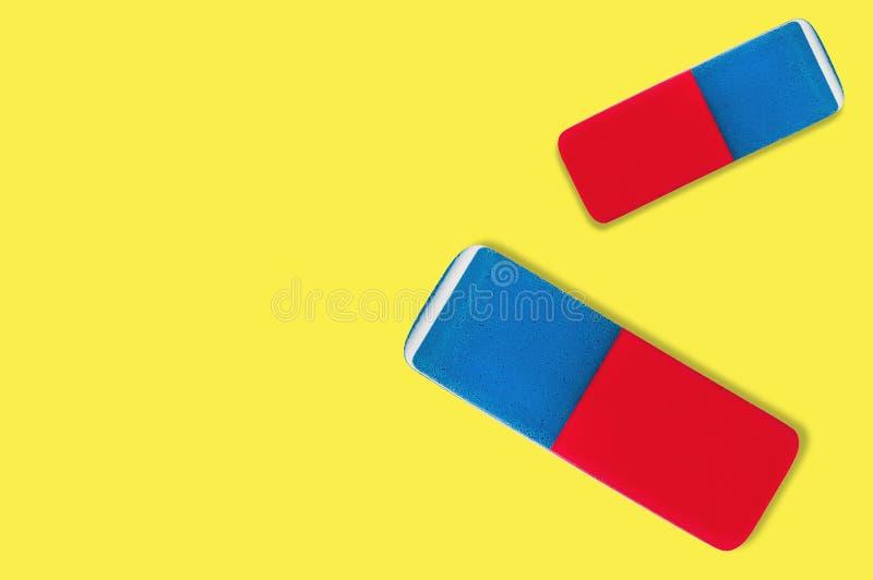 Pares de borradores de goma rectangulares para el lápiz y la tinta de la pluma en fondo amarillo imágenes de archivo libres de regalías