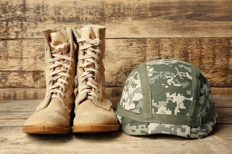Pares de botas de combate e de capacete militar no fundo de madeira, foto de stock royalty free