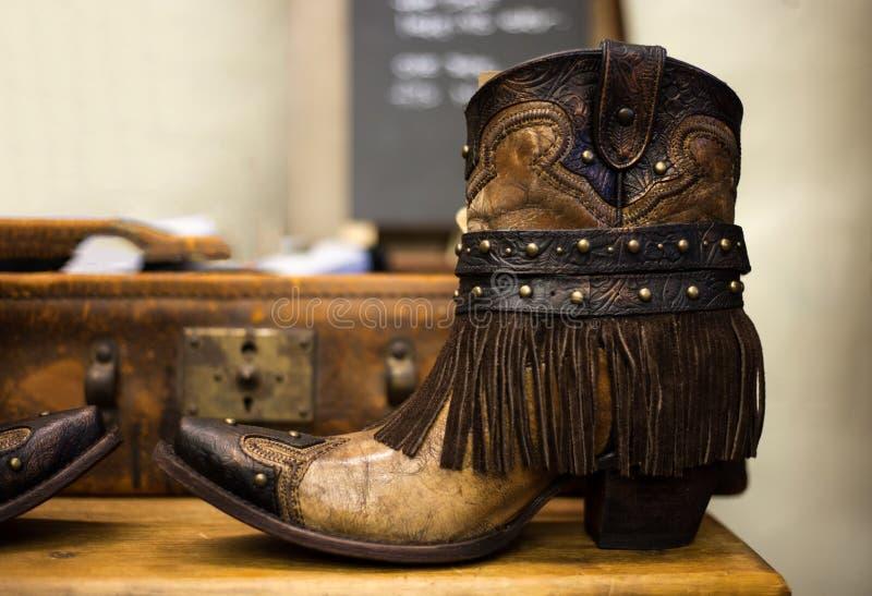 Pares de botas de couro marrons feitos a mão da vaqueira com suitca do vintage foto de stock