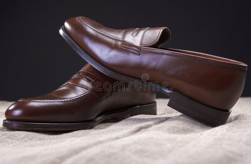 Pares de Brown Penny Loafer Shoes Placed On de cuero elegante Mesh Surface Against Black Background imágenes de archivo libres de regalías