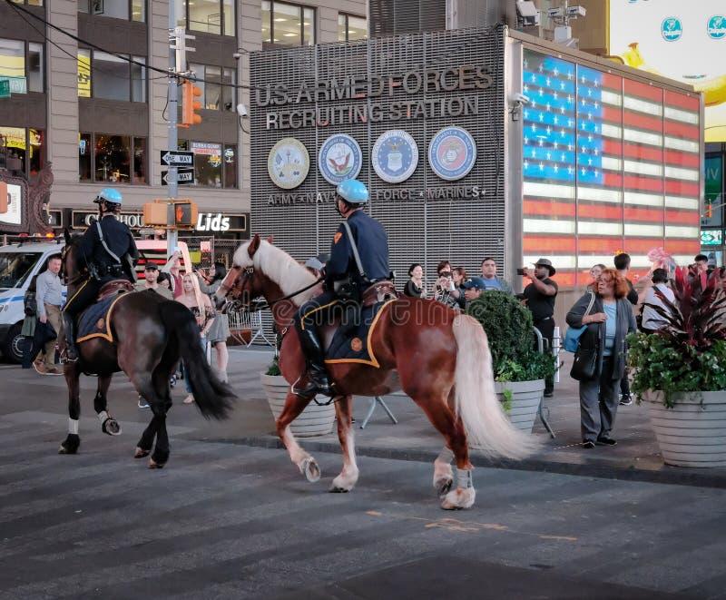 Pares de caballos y allí de jinetes de la policía de NYPD vistos en la patrulla en Times Square, New York City, los E.E.U.U. imagen de archivo