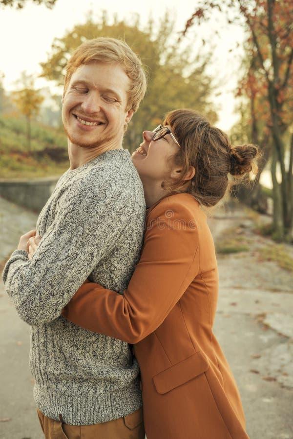 Pares de cabelo vermelhos bonitos de homem e de mulher no equipamento ocasional em uma data Eles que andam no parque do outono qu fotografia de stock royalty free
