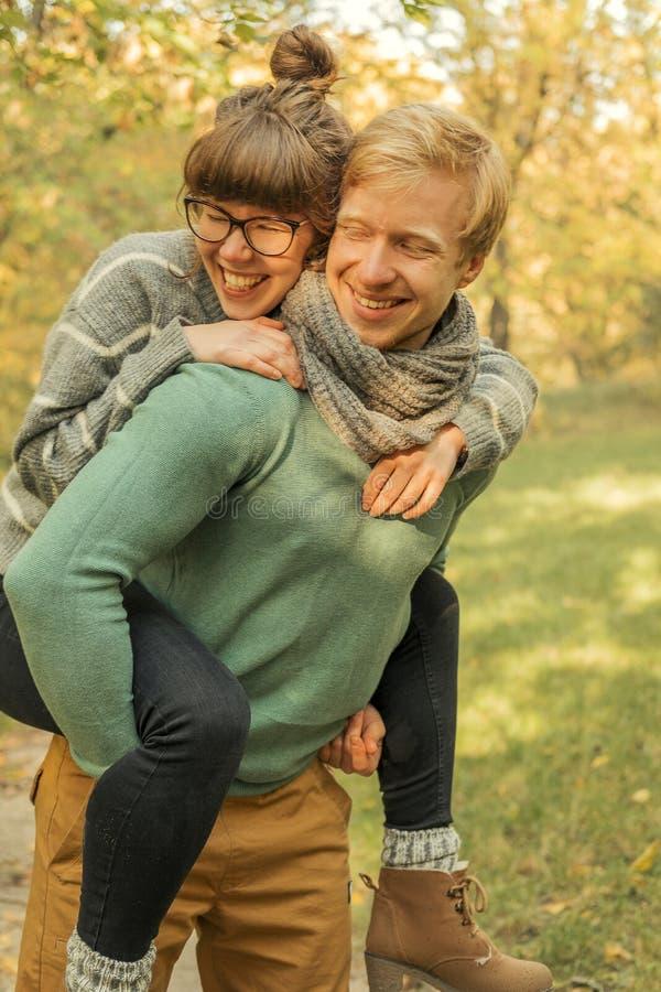 Pares de cabelo vermelhos bonitos de homem e de mulher no equipamento ocasional em uma data Eles que andam no parque do outono qu imagens de stock