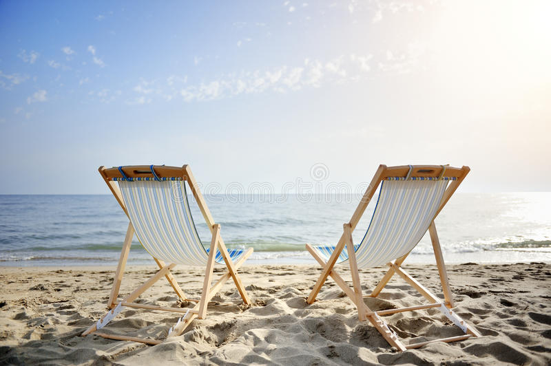 Pares de cadeiras no Sandy Beach no por do sol que procura o mar - conceito do abrandamento fotos de stock royalty free