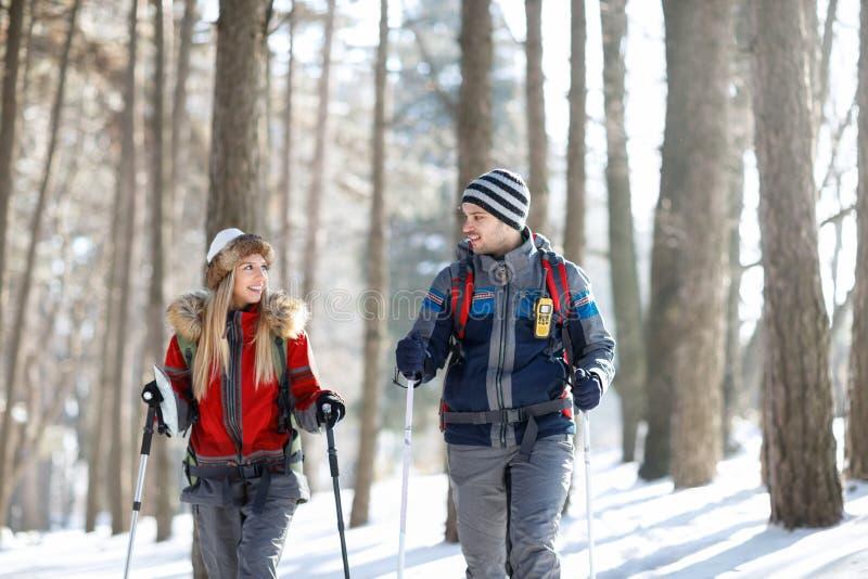Pares de caminantes en el invierno que camina junto imagen de archivo