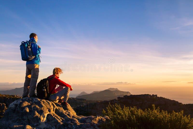 Pares de caminhantes com trouxas que apreciam a vista panorâmica do por do sol nas montanhas, curso fotos de stock