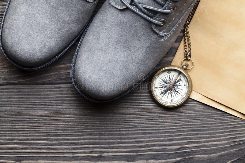 Pares de caminhar botas, a folha de papel feito a mão e o compasso do vintage na tabela de madeira imagens de stock royalty free