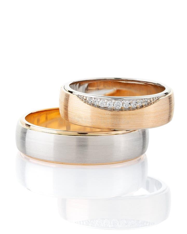 Pares de casarse el anillo de plata y el anillo de oro rosado adornados con los diamantes aislados en el fondo blanco foto de archivo libre de regalías