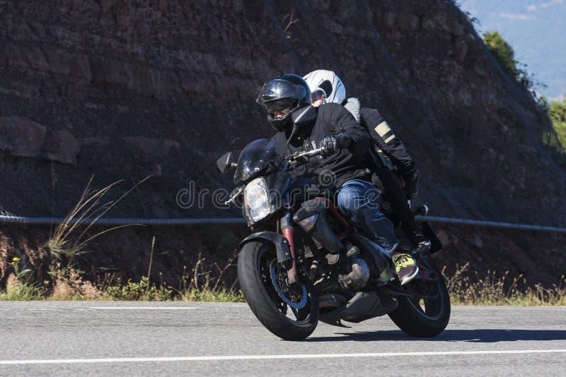 Pares de cavaleiros do motociclista em uma estrada secundária imagens de stock royalty free