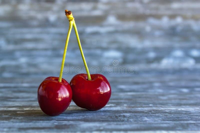 Pares de cerejas vermelhas na tabela de madeira imagem de stock royalty free