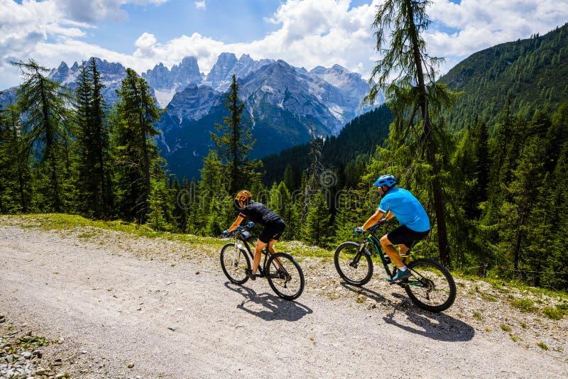 Pares de ciclagem da montanha com as bicicletas na trilha foto de stock royalty free
