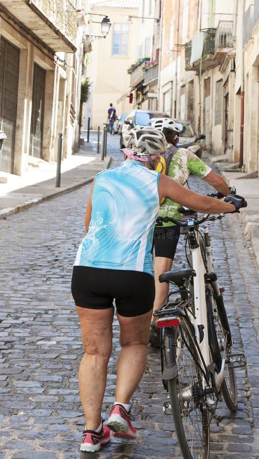 Pares de ciclistas idosos na rua da cidade velha fotografia de stock royalty free