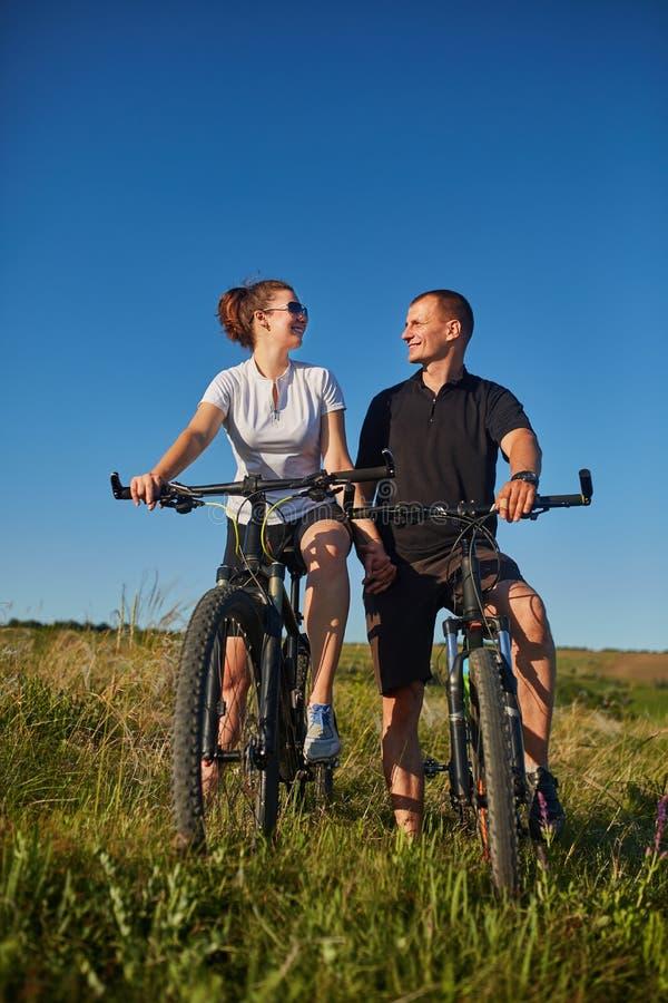 Pares de ciclistas que montam bicicletas no prado fotografia de stock