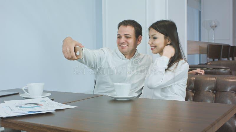 Pares de colegas do negócio que tomam selfies engraçados no telefone em um café foto de stock royalty free