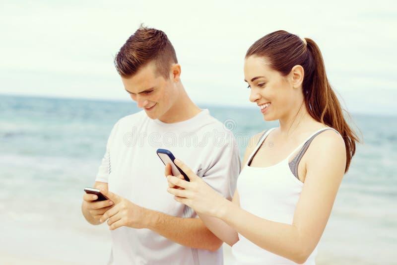 Pares de corredores com os telefones espertos móveis fora foto de stock royalty free