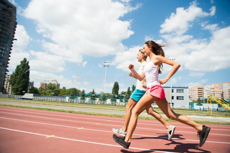 Pares de corredores em exterior ensolarado Mulher e homem corridos no estádio Atividade e energia Formação e exercício no ar fres imagens de stock