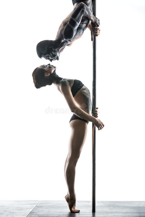 Pares de dançarinos do polo com arte corporal no pilão foto de stock