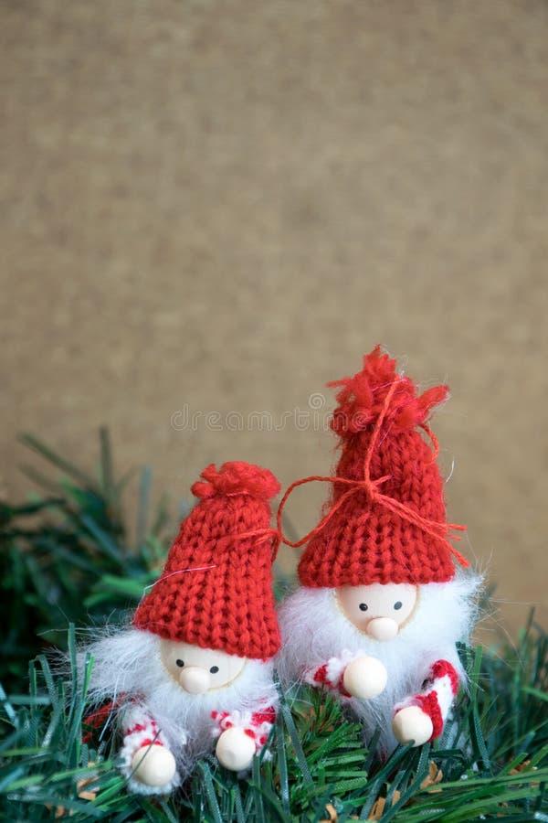 Pares de decoraciones traviesas del duende de la Navidad que suben a través del verdor del tejo imagen de archivo libre de regalías