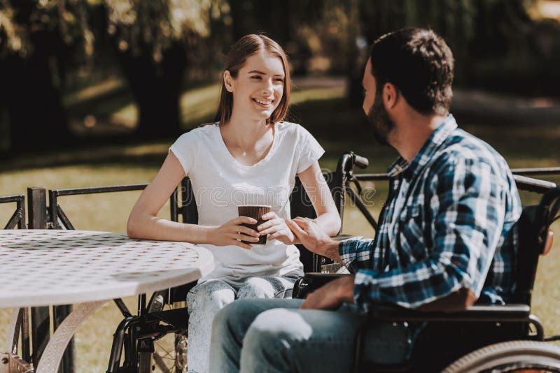 Pares de deficientes motores em cadeiras de rodas no parque fotografia de stock royalty free