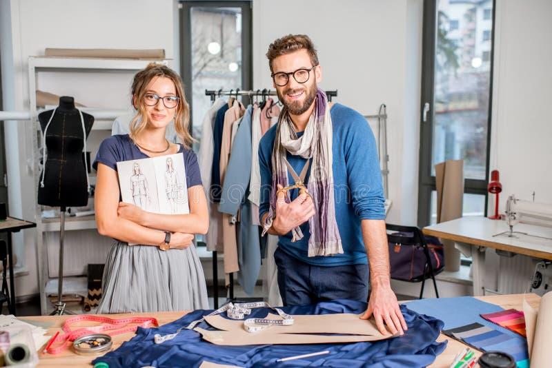 Pares de desenhadores de moda que trabalham no estúdio fotos de stock royalty free