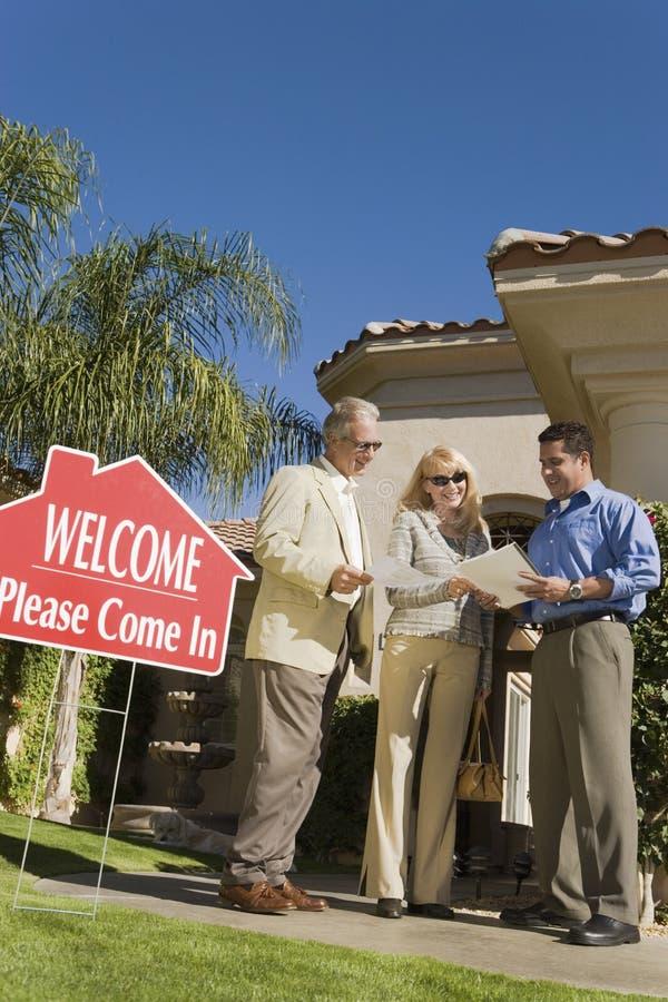 Pares de Discussing Contract With do mediador imobiliário foto de stock