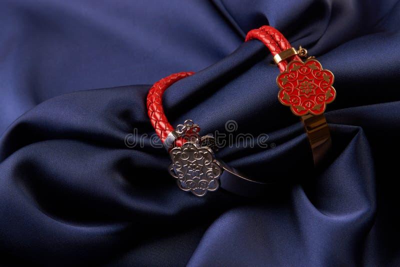 Pares de dois anéis do bijouterie da joia no fundo de seda azul foto de stock
