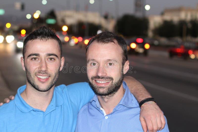 Pares de dois homens que apreciam a vida noturna da cidade fotografia de stock royalty free