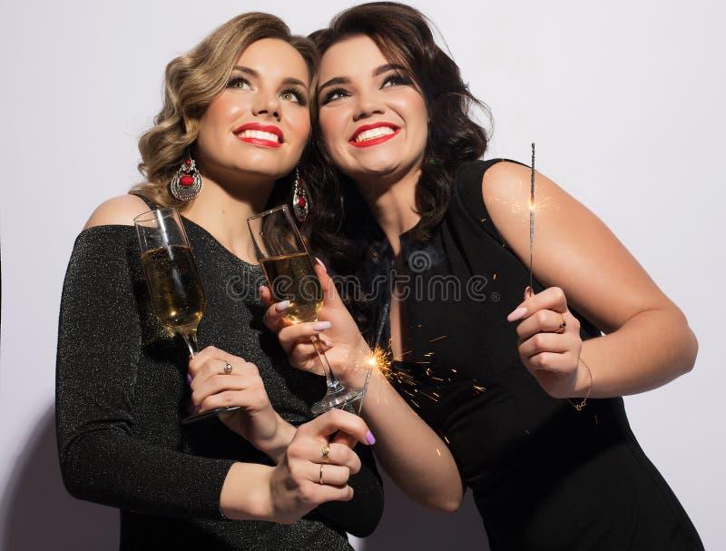 Pares de dos Rich Women Laughing con el cristal de Champán lujo Party el tiempo imagen de archivo