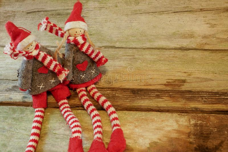 Pares de duendes adorables y lindos de la Navidad - muchacho y muchacha - que se sientan en tabla de madera rústica Con el espaci foto de archivo