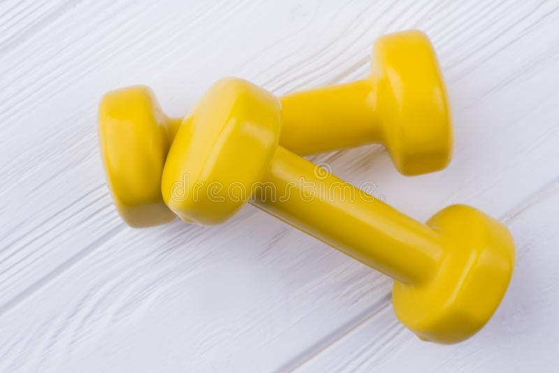 Pares de dumbells amarelos no fundo de madeira branco fotos de stock