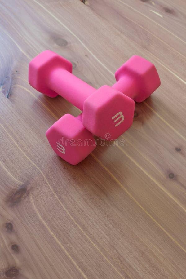 Pares de dumbells de pouco peso cor-de-rosa em uma posição cruzada sobre um fundo de madeira claro, espaço da cópia imagens de stock