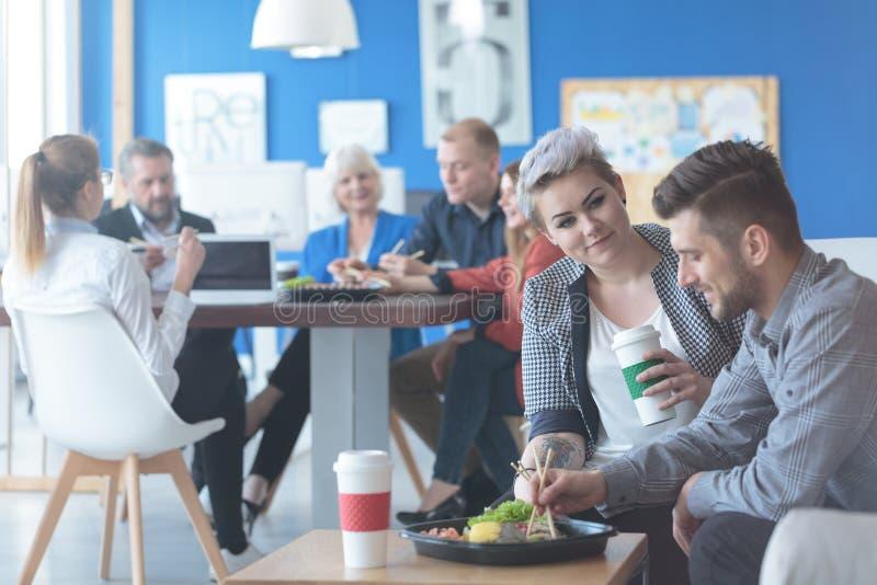 Pares de empleados que comen el almuerzo fotografía de archivo